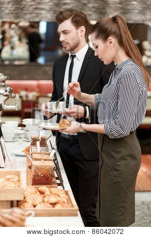 Business managers take croissants and jam at the buffet