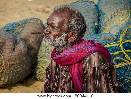 Unidentified old fisherman smoking on Marina beach