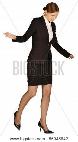 Business woman standing on one leg and looking down
