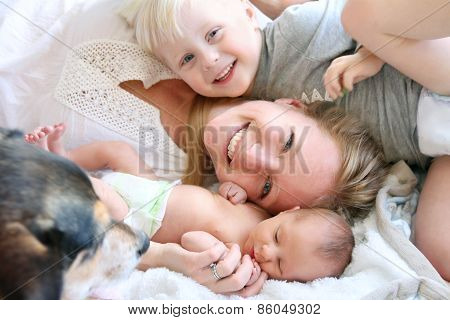 Happy Mother Laying In Bed With Toddler Son And Newborn Baby