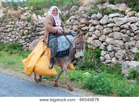 Olderly Woman Carries Yellow Bags On A Donkey