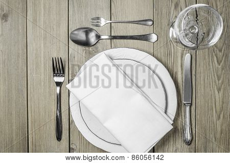 Empty plates with a napkin dining room and cutlery set on a wooden background