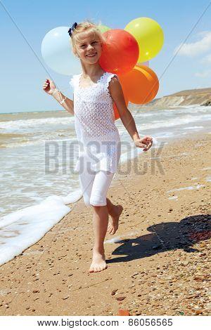 Little Girl Runs Along The Coastline With Balloons