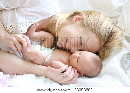 Happy Young Mother Snuggling Newborn Baby Daughter In Bed