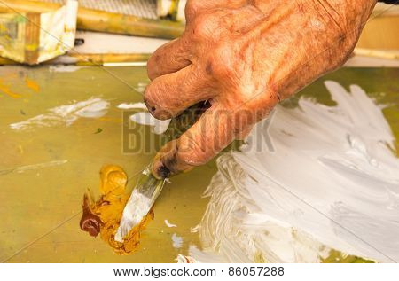 Senior Woman Mixing Oil Paint With Spatula, Closeup Of Hand