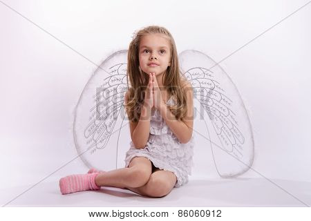 Seated Girl With Angel Wings Folded Hands