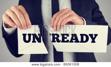 Conceptual Businessman Tearing A White Paper With Unready - Ready Message
