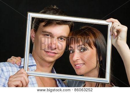 Young couple having fun making faces through frame
