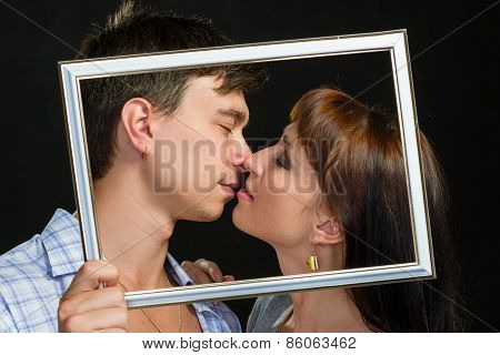 Young couple having fun making faces through frame