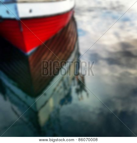 Defocused Red Boat Reflecting In Water