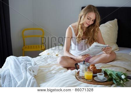 Happy smiling blond in white bed