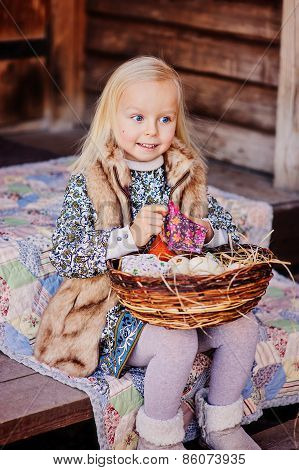 happy child girl playing with easter decorations at country house