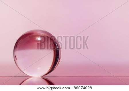 Glass transparent ball on light pink background and mirror surface.
