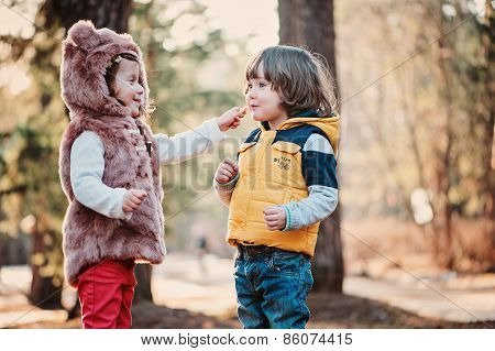 happy toddler friends playing in sunny forest