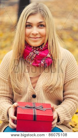 Young Woman With Present In Autum Park
