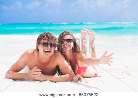 happy young couple lying on a tropical beach in Barbados