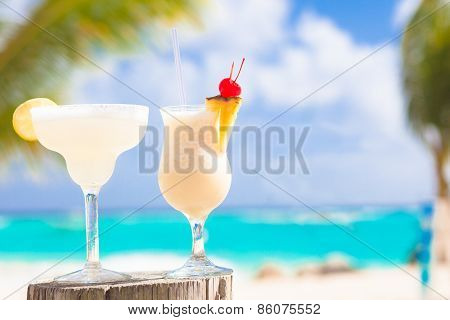 two perfect cocktails pina colada and margarita with cherry on top, beach background