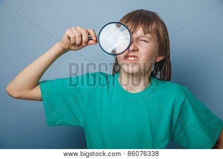 European-looking boy of ten years holding a magnifying glass, a keen eye on gray background