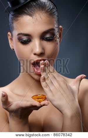 Excited woman looking at precious stone handheld, looking surprised, wearing luxury makeup with strasses.