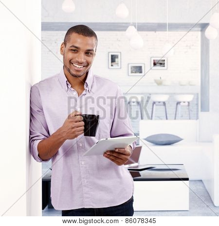 Young black man standing at home leaning against wall, holding tablet, drinking tea, smiling happy.