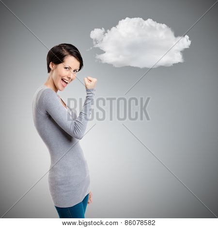 Young happy girl gestures fist on grey background