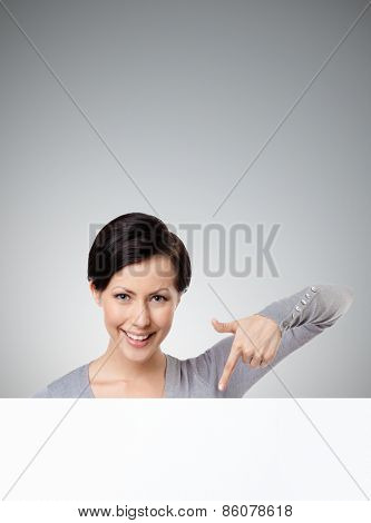 Young woman points down with forefinger , isolated on grey