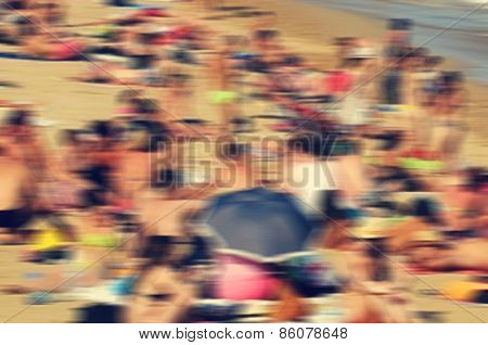 a defocused blur background of a packed beach in the summer