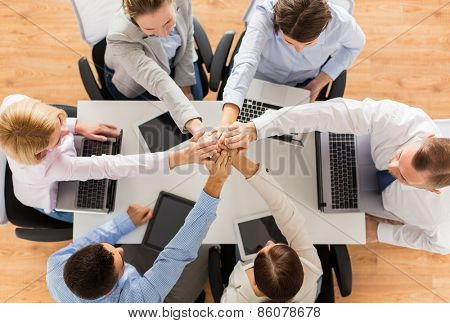 business, people, technology, cooperation and team work concept - close up of creative team with laptop and tablet pc computers sitting at table and holding hands on top of each other in office