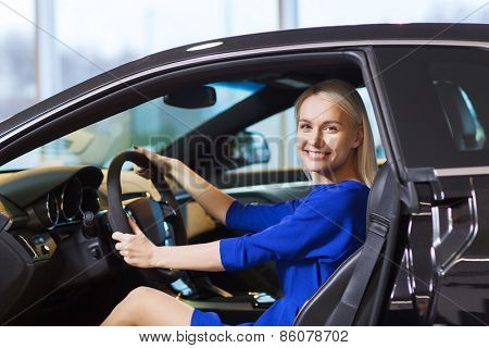 auto business, car sale, consumerism , transportation and people concept - happy woman sitting inside car in auto show or salon