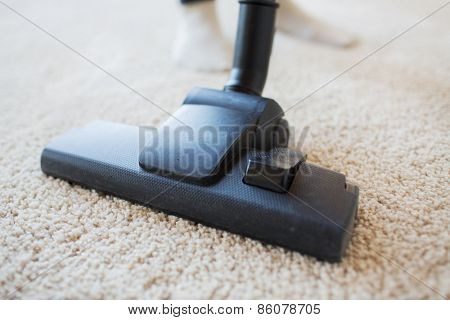 people, housework and housekeeping concept - close up of vacuum cleaner nozzle cleaning carpet at home