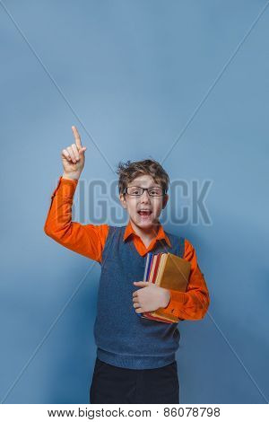 European-looking  boy of ten years  in glasses thumbs up, the idea of the book on a gray background
