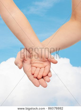 people, charity, family, children and advertisement concept - close up of woman and little child hands holding empty palms over blue sky and cloud background