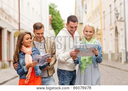 travel, vacation and friendship concept - group of smiling friends with city guide and map exploring city