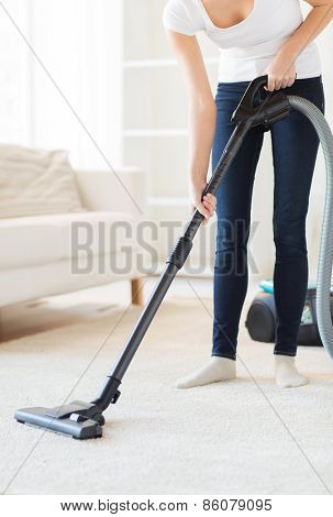 people, housework and housekeeping concept - close up of woman with vacuum cleaner cleaning carpet at home