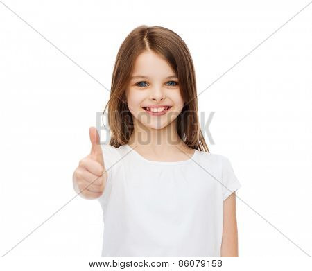 t-shirt design and happy people concept - smiling little girl in blank white t-shirt showing thumbs up