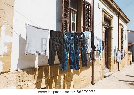Clothes hanging on the line along windows.