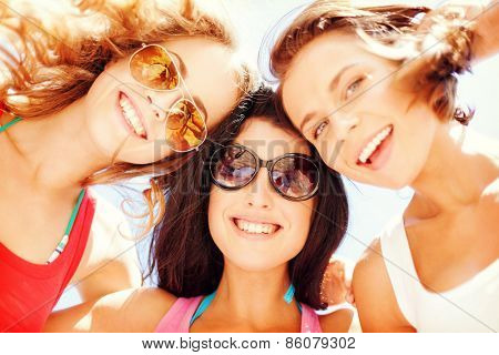 summer holidays and vacation - girls faces with shades looking down