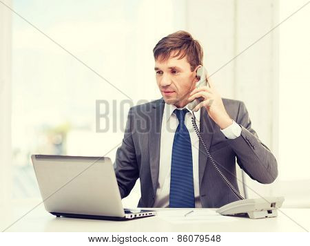 technology, business, education and office concept - handsome businessman working with laptop computer, phone and documents