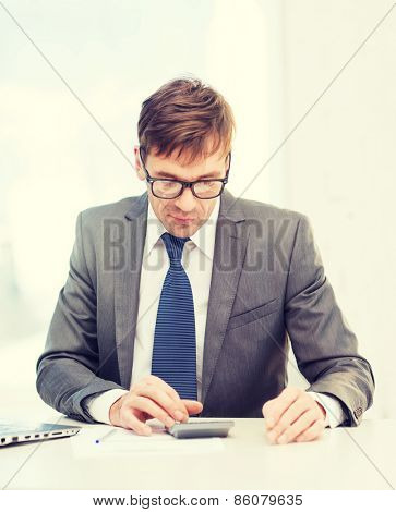 business, office, school and education concept - businessman with papers and calculator