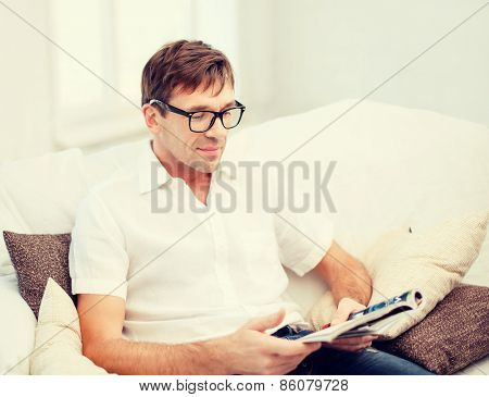 leisure, education and lifestyle concept - man with magazine at home