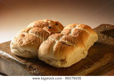 Creatively lit Hot Cross buns on rustic wooden board