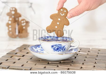 Gingerbread man being dunked into a cup of tea with jar of cookies in the background