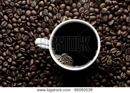 Top view of coffee cup on coffee beans