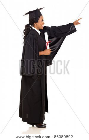 side view of happy female african graduate pointing empty space on white background