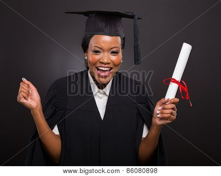 excited african university student holding her graduation certificate