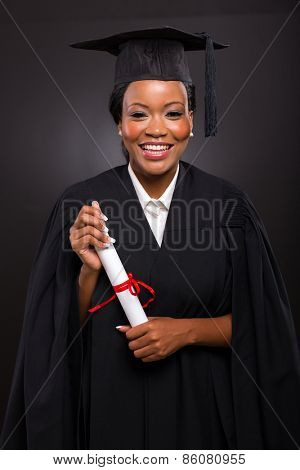pretty african american female student with graduation certificate on black background