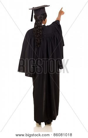rear view of female graduate pointing isolated on white background