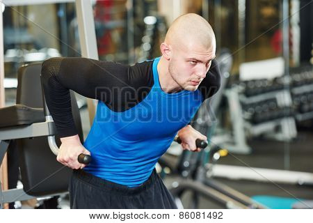 bodybuilder man doing exercises with weight training equipment on sport gym club
