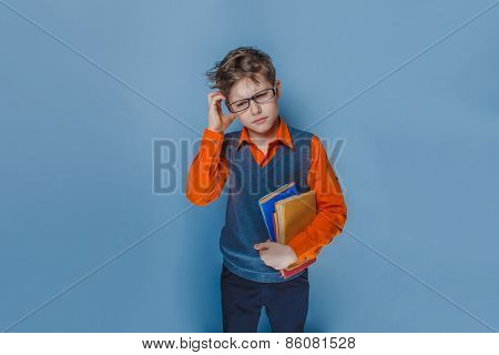 European-looking boy of ten years in glasses thinking intently book on a blue background
