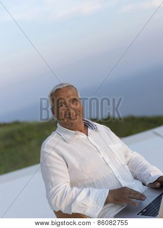 relaxed white hair senior man looking sunset from luxury balclony home and working on laptop computer